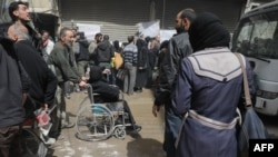 Des civils syriens attendent leur évacuation par le Croissant-Rouge syrien dans l'enclave de la Ghouta orientale, Syrie, 22 mars 2018,