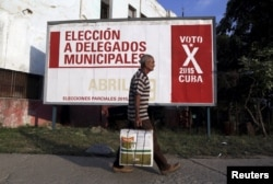 A man walks past near a poster announcing Cuba's municipal elections, to be held April 19, in Havana, Cuba, April 6, 2015.