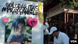 Wakil Walikota Solo menuliskan ungkapan duka cita di aksi Pray For Angeline di ajang Car Free day Solo, Minggu pagi. (VOA/Yudha Satriawan)