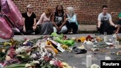 Mujeres se sentaron frente a un improvisado memorial en recuerdo de las vícitimas del ataque con un automóvil que tuvo lugar el 12 de agosto de 2017.