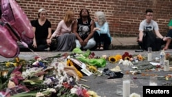 "Women sit by an impromptu memorial of flowers commemorating the victims at the scene of the car attack on a group of counterprotesters during the ""Unite the Right"" rally as people continue to react to the weekend violence in Charlottesville, Va., Aug. 14,"
