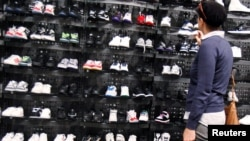 FILE - A woman shops inside a Foot Locker store in New York, May 28, 2010.