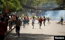 FILE - Protesters run from tear gas being fired by police during Irreecha, the thanks giving festival of the Oromo people in Bishoftu town of Oromia region, Ethiopia, Oct. 2, 2016.