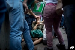 Irama Carrero is aided by fellow shoppers after fainting in a food line outside a grocery store, in the afternoon in Caracas, Venezuela, May 5, 2016.