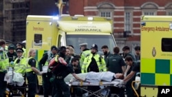 Emergency services transport an injured person to an ambulance, close to the Houses of Parliament in London, March 22, 2017.