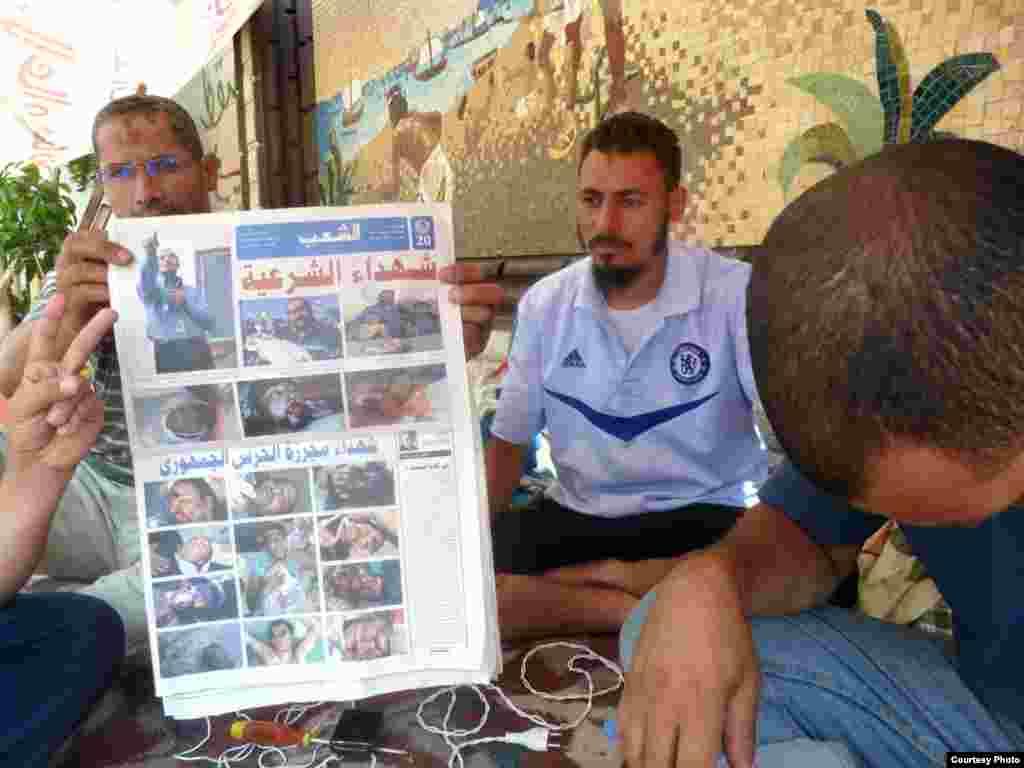 Các bác sĩ nhóm Huynh đệ Hồi Giáo trưng ra tờ báo có hình những người ủng hộ họ bị giết trong một cuộc đối đầu với quân đội Ai Cập 8-7-2013. Ảnh: VOA/Sharon Behn
