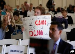 FILE - Benjamin Tuggy holds a sign while listening to speakers during the first of three public hearings on the Trump administration's proposal to roll back car-mileage standards in a region with some of the nation's worst air pollution in Fresno, Calif., Sept. 24, 2018.