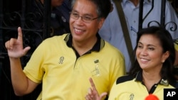 "Presidential candidate Mar Roxas and running mate Maria Leonor ""Leni"" Robredo flash the ""L"" sign for ""Laban"" meaning Fight! after filing their certificates of candidacy for next year's presidential elections, Oct. 15, 2015 in Manila."