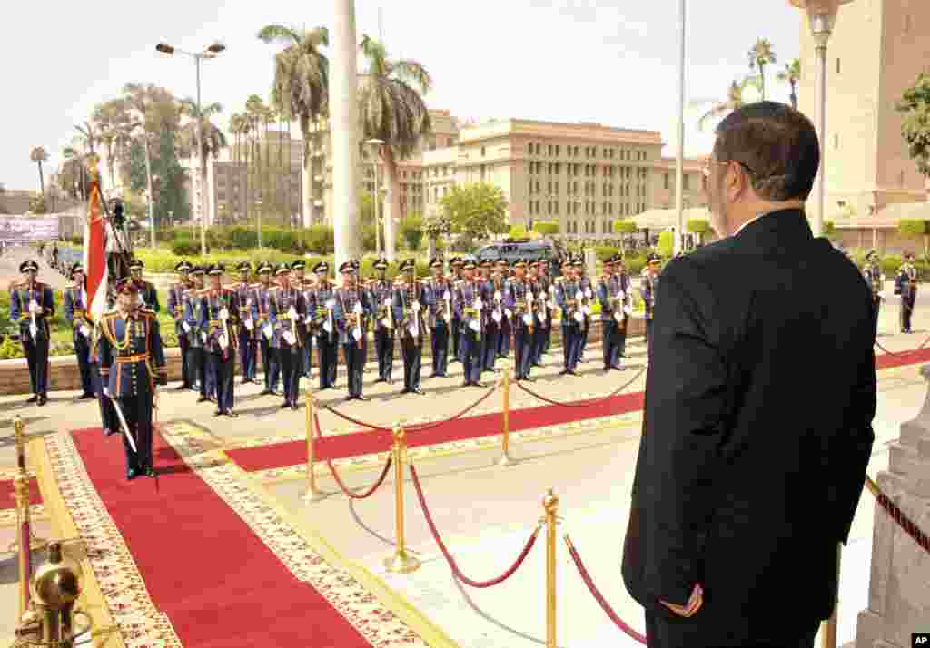 Egyptian President Mohammed Morsi stands before a military honor guard after his inauguration in Cairo, Egypt, June 30, 2012.