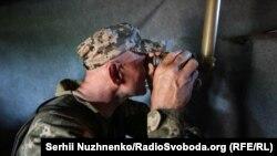 Український військовий дивиться у бінокль на позиції біля Станиці Луганської на сході України (ілюстраційне фото)