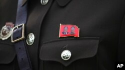 A North Korean guide wears a pin with the photos of late North Korean leaders Kim Il Sung at left and Kim Jong Il at right, Aug. 17, 2018, at the Samjiyon Great Monument in Samjiyon, North Korea.
