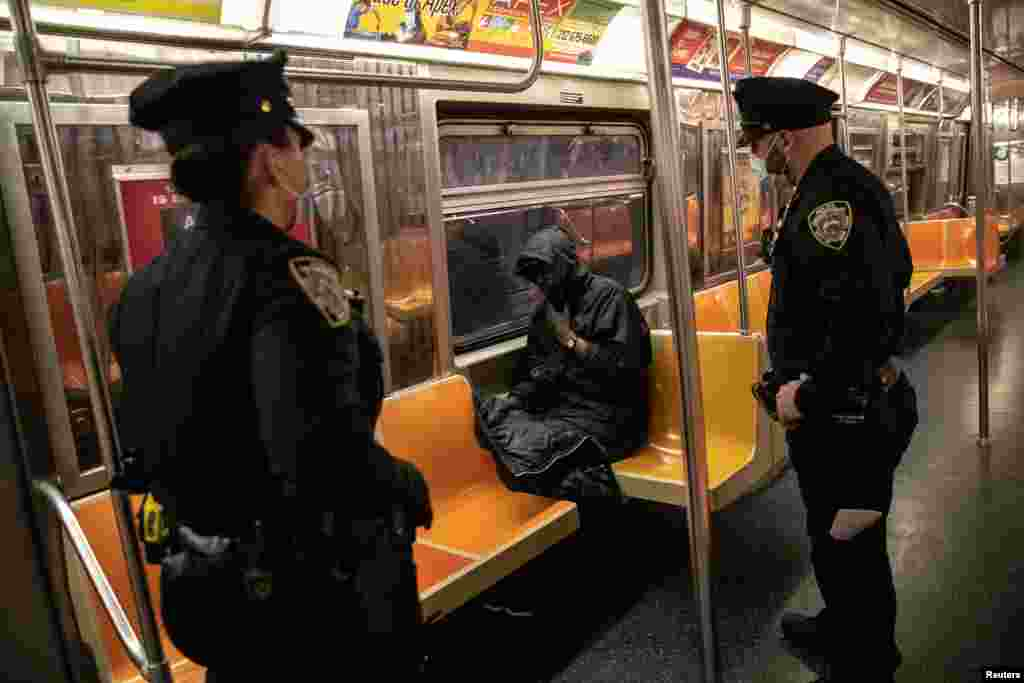 New York City Police (NYPD) officers wake up a passenger on a subway train.