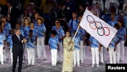 FILE - Tokyo governor Yuriko Koike waves the Olympic flag as International Olympic Committee (IOC) President Thomas Bach applauds at the closing ceremony of the 2016 Rio Olympics in Rio de Janeiro, Brazil, Aug. 21, 2016.