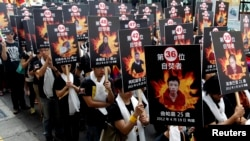 FILE - Activists displaying portraits of people who killed themselves via self-immolation take part in a rally to support Tibet in Taipei, March 10, 2013.