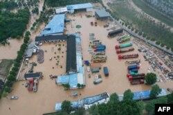 Bangunan dan kendaraan yang terendam banjir akibat hujan lebat di kawasan Shexian, kota Huangshan, provinsi Anhui China bagian timur, 7 Juli 2020.