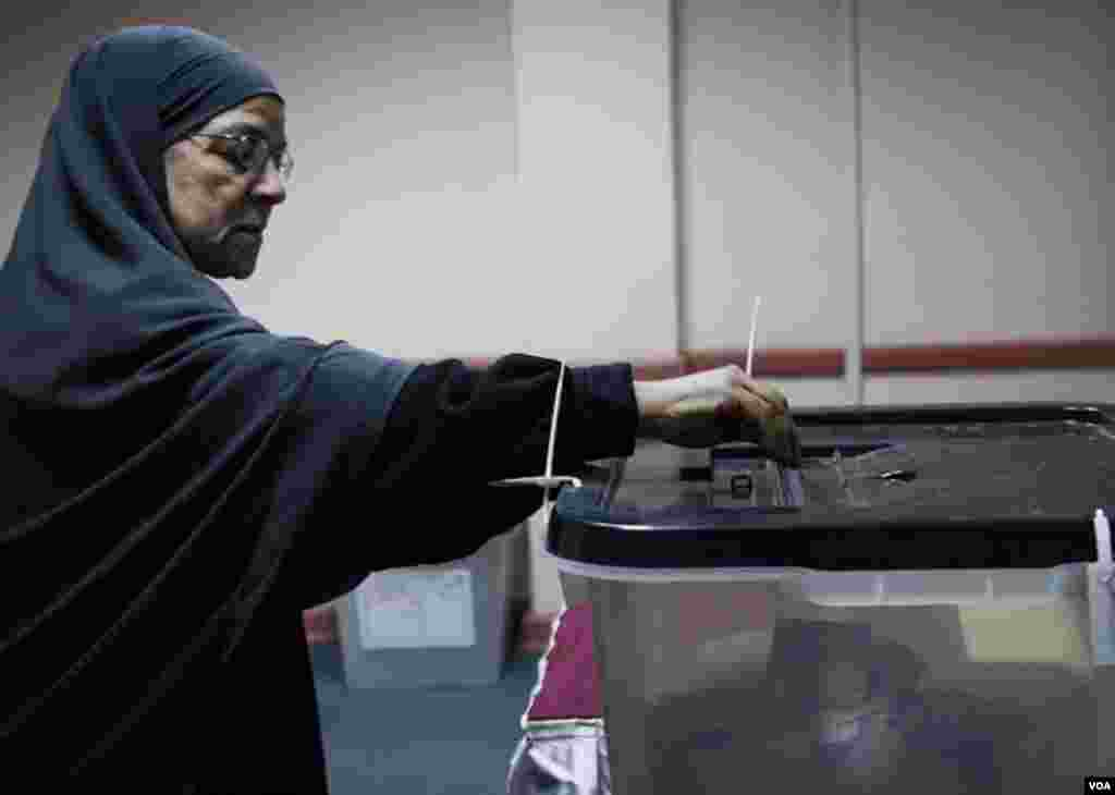 Seorang perempuan memasukkan kertas suara di Giza (22/12). (VOA/Yuli Weeks)