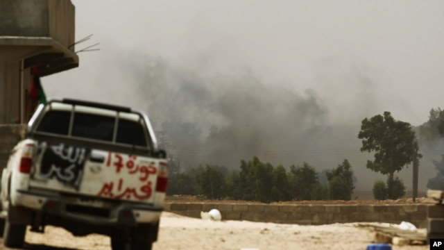 Smoke rises after a rocket exploded near a Libyan rebel fighter position on the outskirts of Zlitan near Misrata's western front line