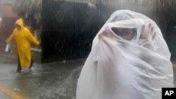 Una mujer cubre con una bolsa plástica de la lluvia al acerarse el huracán María a República Dominicana.