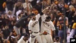 Los jugadores de los Gigantes, Brandon Belt y Pablo Sandoval, chocan cinco en el aire, tras derrotar a los Nacionales de Washington.