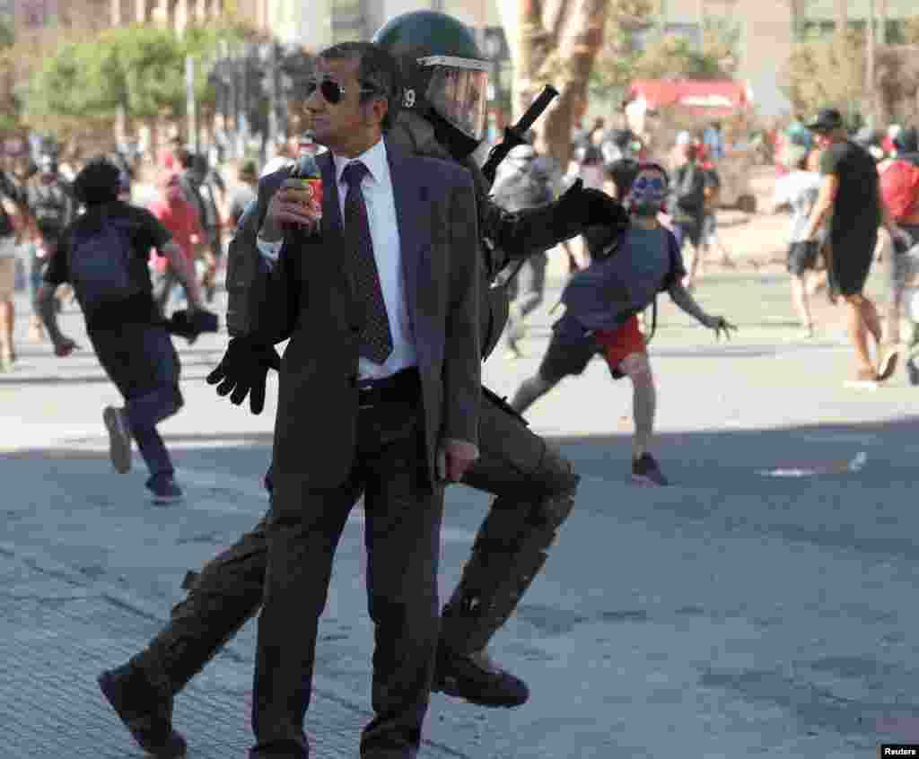 A man drinks a Frucola as a policeman chases demonstrators during a protest against Chile's government in Santiago, Dec. 4, 2019.
