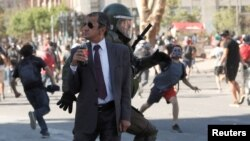 Policía persigue a los manifestantes durante una protesta contra el gobierno de Chile en Santiago, Chile.