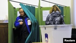 A Slovenian couple votes during the second round of presidential elections at a polling station in Planina, December 2, 2012.