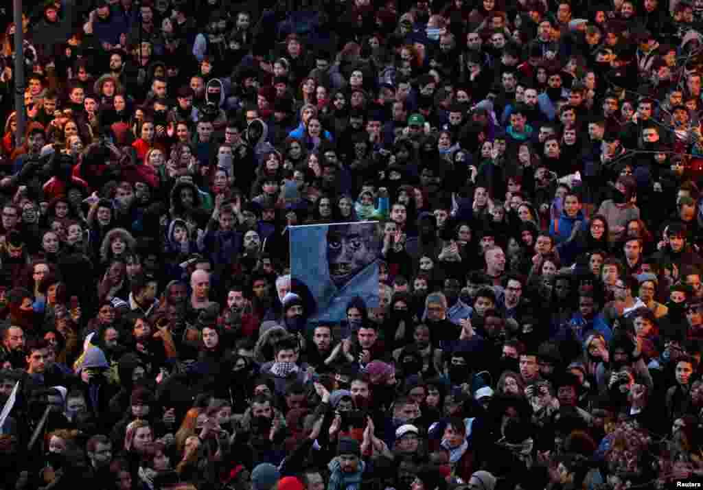 People attend a gathering to protest against the death of a street hawker in central Madrid, Spain.