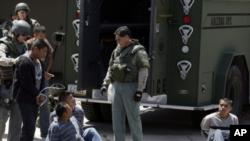 Foto Archivo - Sospechosos de inmigrantes indocumentados son detenidos por agentes de la ley en Phoenix después de allanar una casa jueves, 29 de abril de 2010.