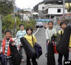 博爱国小学童背起提琴上学去