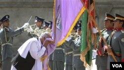 Ashraf Ghani, kepala Komisi Peralihan keamanan, mencium bendera polisi Afghanistan saat penyerahan keamanan di Bazarak, provinsi Panjshir (24/7).