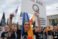 Romanian supporters of QAnon shout slogans against the government's measures to prevent the spread of the COVID-19 infections, like wearing a face mask, during a rally in Bucharest, Romania, Monday, Aug. 10, 2020.