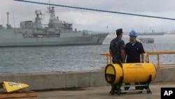 Anggota angkatan laut AS berdiri dekat alat pencari sinyal kotak hitam yang akan digunakan untuk mencari pesawat Malaysia Airlines penerbangan MH370 di Perth, Australia (30/3). (AP/Rob Griffith)