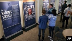 "Princeton University students walk through an exhibit titled, ""In the Nation's Service? Woodrow Wilson Revisited,"" April 3, 2016, at the Woodrow Wilson School of Public and International Affairs in Princeton, New Jersey."