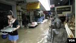 Seorang remaja berjalan di sebuah gang di tengah banjir parah di Thailand.