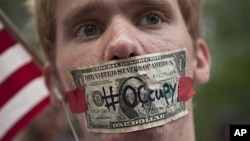 "A protester affiliated with the ""Occupy Wall Street"" protests stands with a US dollar bill taped over his mouth in Zuccotti Park in New York, October 10, 2011."