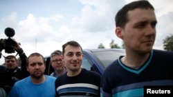 OSCE observers stand on a road 30 km (19 miles) from Donetsk in eastern Ukraine, May 3, 2014, after being freed.