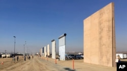 People look at prototypes of a border wall, Oct. 26, 2017, in San Diego. Contractors have completed eight prototypes of President Donald Trump's proposed border wall with Mexico, triggering a period of rigorous testing to determine if they can repel sledgehammers, torches, pickaxes and battery-operated tools.