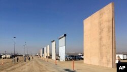 FILE - People look at prototypes of a border wall, Oct. 26, 2017, in San Diego. Contractors have completed eight prototypes of President Donald Trump's proposed border wall with Mexico, triggering a period of rigorous testing to determine if they can repel sledgehammers, torches, pickaxes and battery-operated tools.