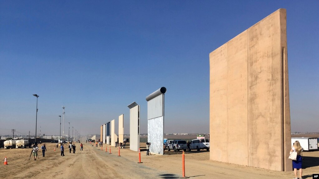 FILE - People look at prototypes of a border wall, Oct. 26, 2017, in San Diego, California. Contractors have completed eight prototypes of President Donald Trump's proposed border wall with Mexico, triggering a period of rigorous testing.