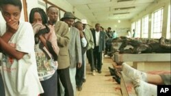 Warga Kenya berjalan dalam antrean di kamar mayat kota Nairobi mencoba mengidentifikasi kerabat dan teman, Sabtu, 8 Agustus 1998. Sebuah bom kuat meledak Jumat di samping kedutaan besar AS di Nairobi. (Foto: AP).