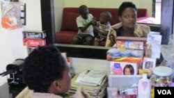 A customer waits for her hair stylist in Rita Dantaa's hair salon in downtown Johannesburg, May 16, 2014 (Gillian Parker for VOA).