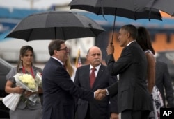 President Barack Obama, right, shakes hands with Cuba's Foreign Minister Bruno Rodriguez