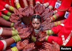 Brides display their hands decorated with henna around a bride as she poses for her own photographer during a mass marriage ceremony in which, according to its organizers, 70 Muslim couples took their wedding vows, in Ahmedabad, India, February 11, 2018.