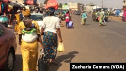 Des femmes quittant un marché de la banlieue de Conakry avec des sacs plastiques, en Guinée, le 17 janvier 2018. (VOA/Zacharia Camara)