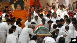 Followers carry the body of spiritual guru Sri Sathya Sai Baba during his funeral inside an ashram at Puttaparti in the southern Indian state of Andhra Pradesh April 27, 2011.