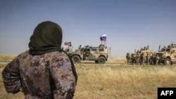 Një grua siriane shikon ushtarët amerikanë dhe rusë pjesën verilindore të Sirisë