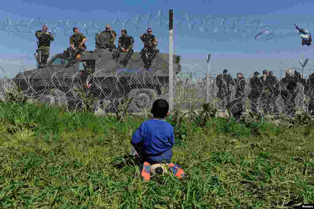 A boy sits on his ball next to a border fence on the Greek side of the border, as Macedonian police stand guard on the Macedonian side, near the Greek village of Idomeni.