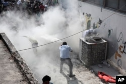 A policeman tries to disperse hundreds of migrants by spraying them with a fire extinguisher during a registration procedure that was taking place at the stadium of Kos town, on the southeastern island of Kos, Greece, Aug. 11, 2015.