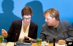 FILE - German Chancellor and chairwoman of the German Christian Democratic Union (CDU), Angela Merkel, right, and Annegret Kramp-Karrenbauer, left, secretary general of the CDU, talk at meeting in Berlin, Germany, Nov. 4, 2018.