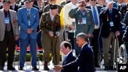 Prezidan Barack Obama ak lidè fransè a, Francois Hollande, ap pase devan veteran yo ak lòt moun kap paticipe nan seremoni kap make 70èm anivèsè Jou J a. (Colleville-sur-Mer, Frans, 6 Juen 2014).